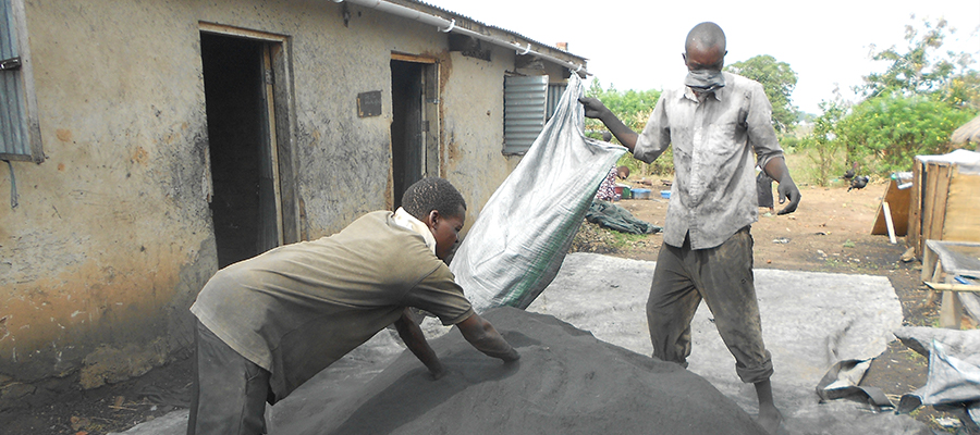 Mixing char and charcoal dust in Soroti, Uganda at Appropriate Energy Saving Technologies (AEST).