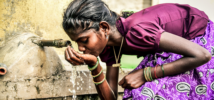 Girl drinking water from a community water tank in Bangalore. Photo: Megha Hegde