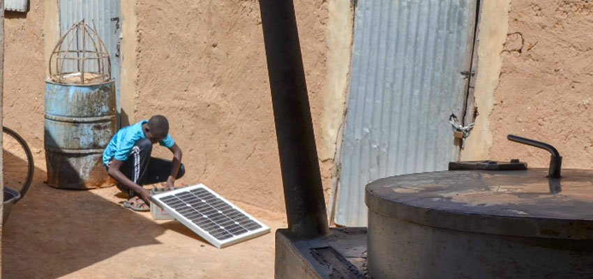 Young man with solar panel in Dioro, Mali.