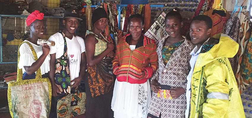 The Kimuli Fashionability team showcases some of its products that it has recently created. The founder, Juliet Namujju (far left), became inspired to blend African fabrics with recyclable materials based on her childhood experience of watching her grandmother practice her trade as a tailor.