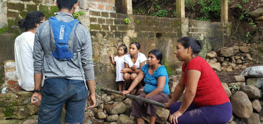 Samir Wadhwania '18 (second from left) and Geovany Moreno talking with the women of El Sauce, El Salvador about to describe how to connect the pipes that would provide them with water for laundry.
