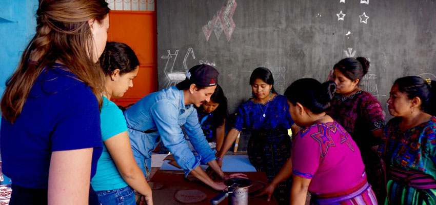 Team member Natalie & Link4 Co-Founder Omar Crespo work with community members on stage 3 of the workshop manipulating cardboard cutouts to determine ideal size of cookstove.